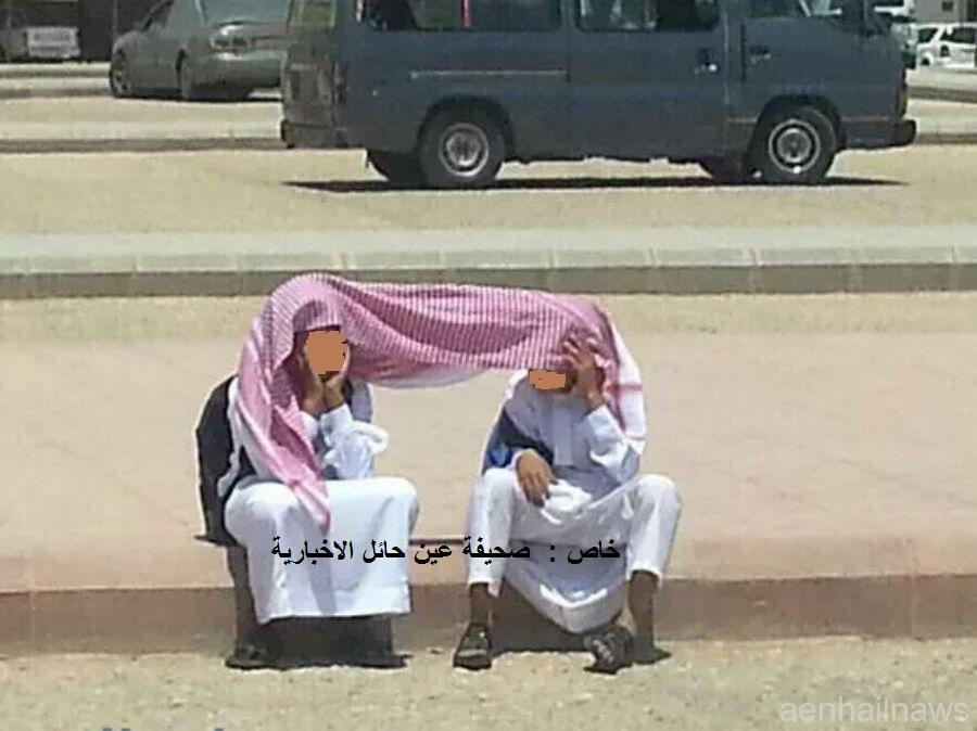 بجوار المدرسة طالبان يحتميان من أشعة الشمس بشماغ واحد