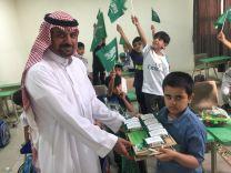 طالب بالصف الأول يهدي معلمه وزملاءه هدايا بمناسبة اليوم الوطني 88 بمدرسة الودي الابتدائية